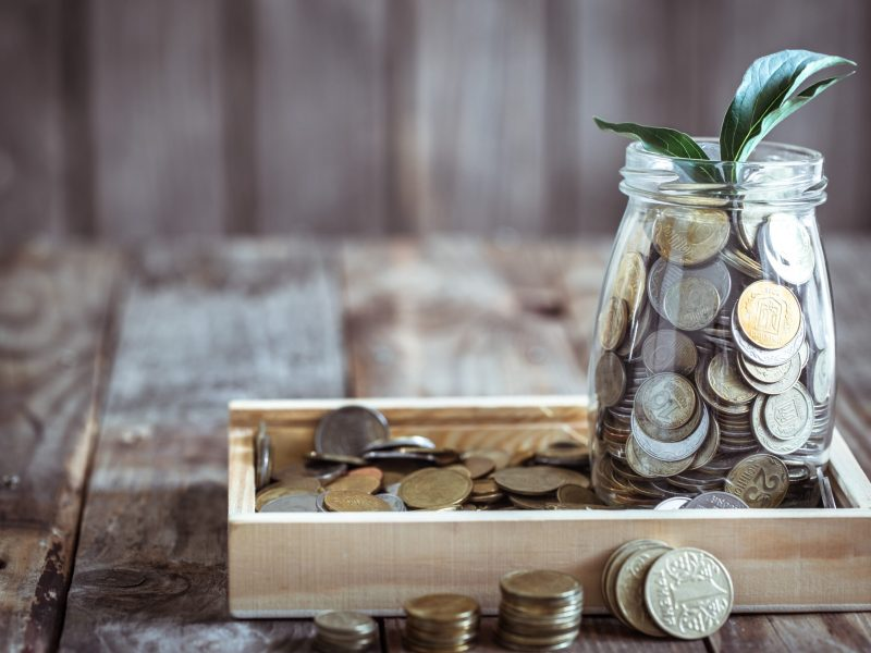 A jar with different coins and green growth growing from above, stand on a wooden background, the concept of growth and saving money